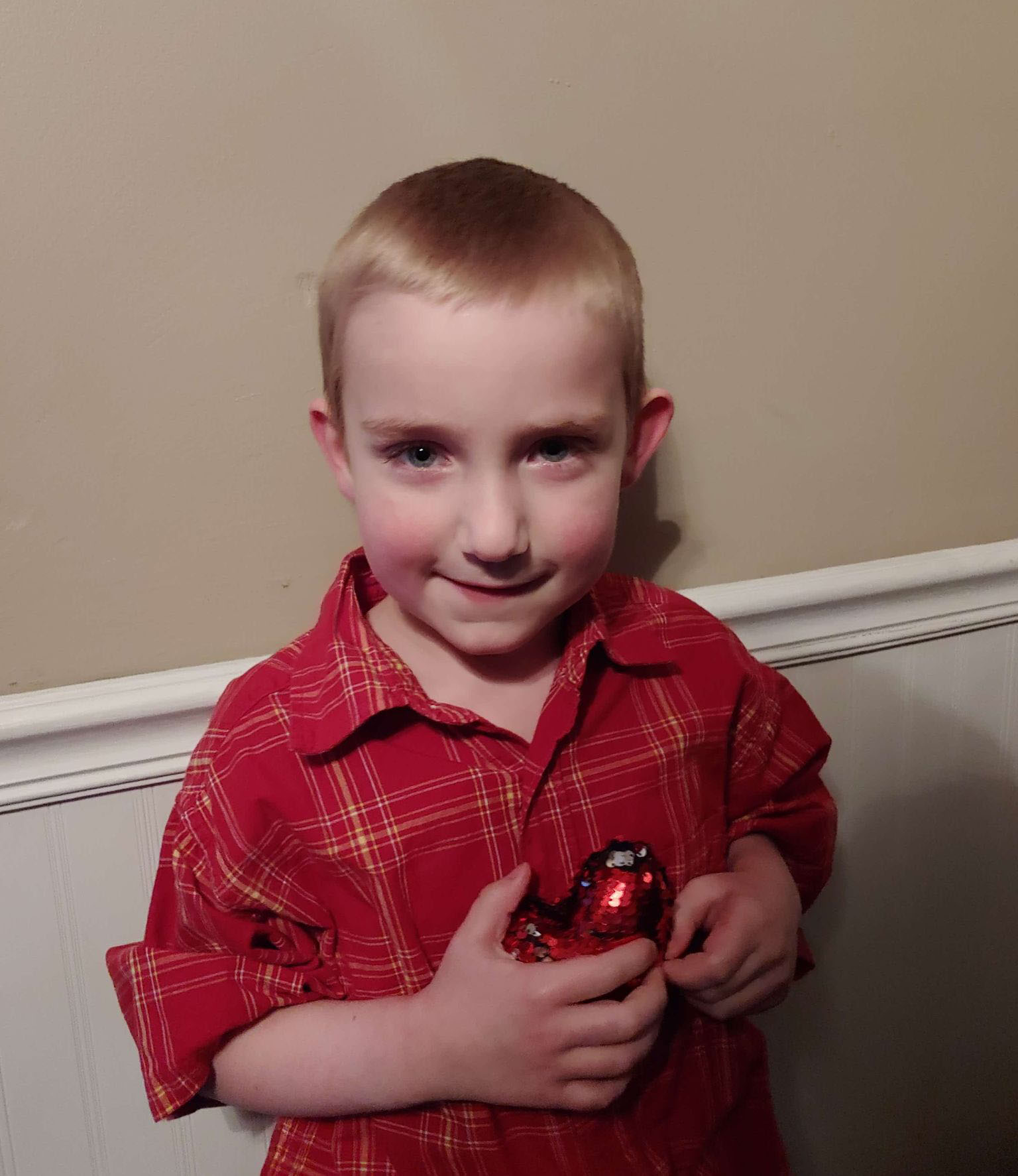 Kyler, a six-year-old Accra client, holding a balloon heart